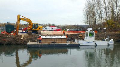 A l'aide de pelles sur ponton :  manutention des fûts de produits pétroliers en sacs étanches, transport fluvial jusqu'à la zone de reprise